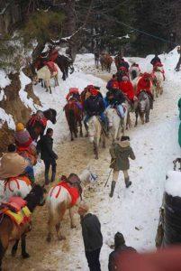 बर्फवारी में घुड़सवारी का आनन्द लेते पर्यटक